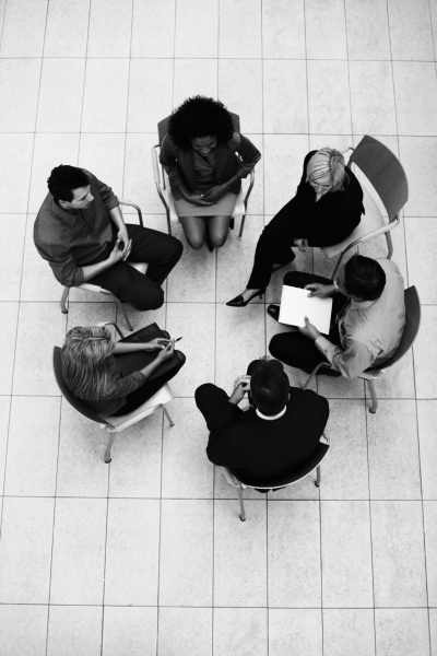 Top view of professionals sitting in circle and discussing business strategy
